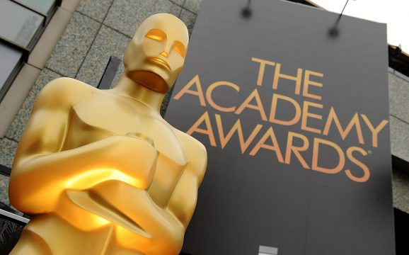 Oscar statue in front of Academy Awards sign