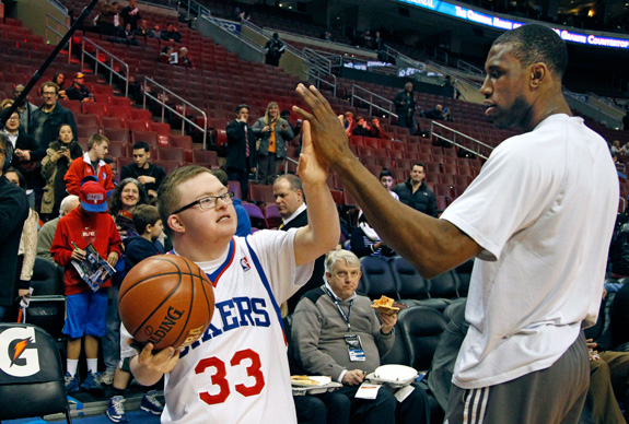 Kevin Grow, left, gave a high-five to Thaddeus Young of the Philadelphia 76ers before a game earlier this month when the teen with Down syndrome was honored by the NBA franchise. Next month, Grow will play with the Harlem Globetrotters. (Ron Cortes/Philadelphia Inquirer/MCT)