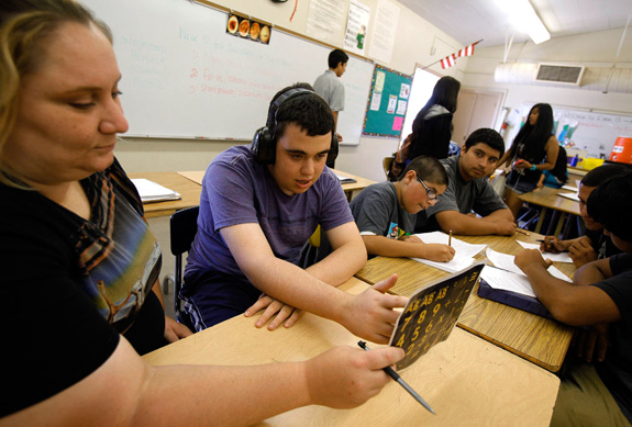 Ido Kedar, center, who has autism, works with Anna Page during a class at Canoga Park High School in Canoga Park, Calif. The NIMH is funding new studies to identify services to help those with autism transition from high school and during other stages of life. (Genaro Molina/Los Angeles Times/MCT)
