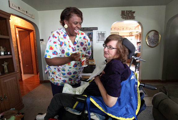 Queen Garner, a home health aide, left, jokes with Susan Werth at Werth's Milwaukee home. A new federal rule taking effect in January will require that most direct care workers are paid at least the federal minimum wage. (Kristyna Wentz-Graff/Milwaukee Journal Sentinel/MCT)