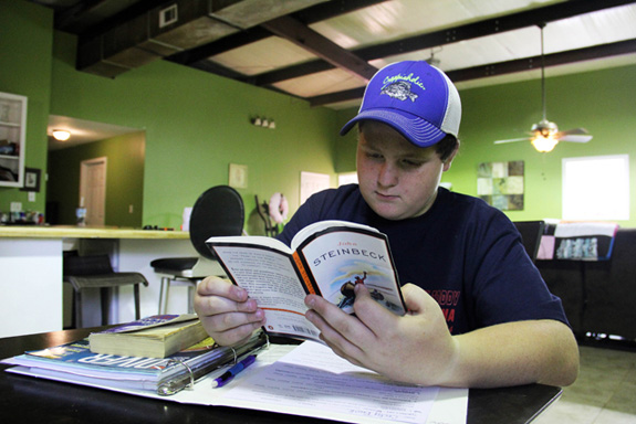 Cody Beck reads a book that was assigned by his teacher. Cody's educational placement has changed numerous times since he was hauled off by police following an incident at school that was determined to be a result of his disability. (Jackie Mader/The Hechinger Report)