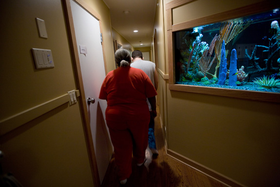 A caregiver assists a man with autism is his home. Starting in 2015, most in-home care workers will qualify for the first time for federal minimum wage and overtime protections. (Charles Cherney/Chicago Tribune/TNS)